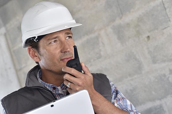 Entrepreneur on building site using walkie talkie